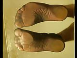 Feet soles pink toes in black and brown nylon socks