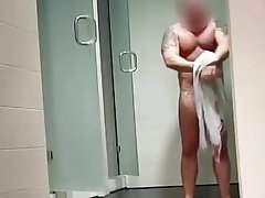 Hung muscle dude steps out of the shower in locker room