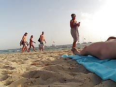 Frauen, die FKK-Mann am Strand fotografieren