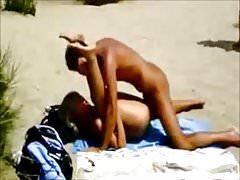Un couple nu baise sur la plage devant des inconnus
