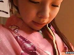 Una bella asiatica in un vestito strofina e si infila le dita nella figa