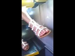 Nettes Hochschulmädchen mit herrlichen Füßen und den Beinen auf dem Bus