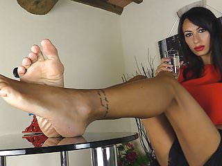 Elegant girl with red sandals shows her bare feet
