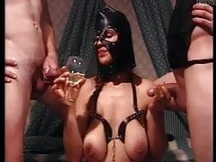Slut with bondage mask drinking piss from a glass