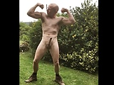 Muscular guy outdoors flexing and wanking